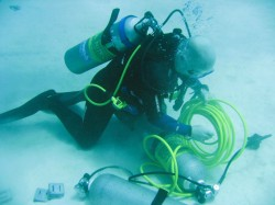 Diver, Rob Hughes on the seabed working with air cylinders and hosepipe to make the bubble curtain